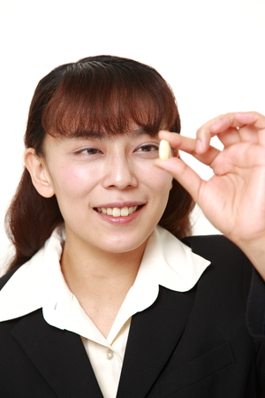 supplement: Asian woman takes a supplement