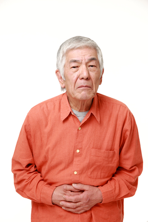 defecation: senior Japanese man suffers from stomachache Stock Photo