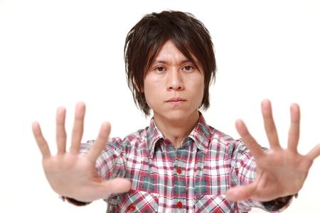 停止ジェスチャーを作る若い日本人男性