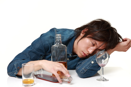 Young Japanese man in depression is drinking alcohol Stock Photo