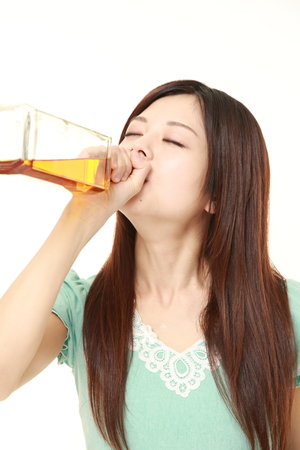 young Japanese woman drinking straight from a bottle