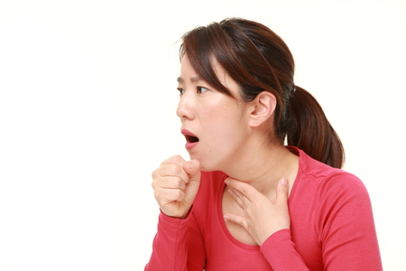 middle aged Japanese businesswoman coughing Stock Photo