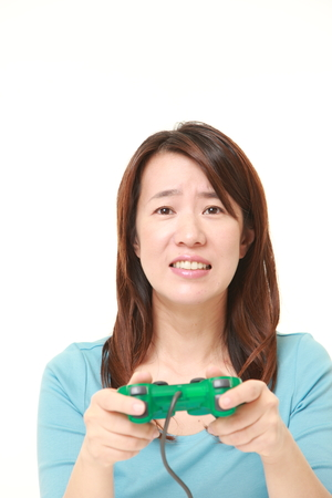 middle aged Japanese woman losing playing video game Stock Photo