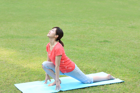 lunge: Japanese woman outside doing yoga High Lunge Stock Photo