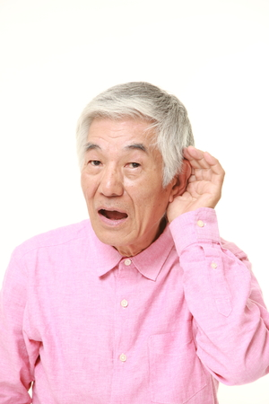 closely: senior Japanese man with hand behind ear listening closely