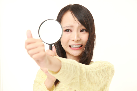 shocked young woman looking through a magnifying glass her nails Stock Photo