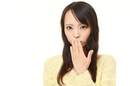 Japanese woman making the speak no evil gesture Stock Photo