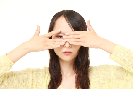 coward: woman covering her face with hands peeping at the camera through her fingers Stock Photo