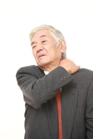 senior man on a neck pain: senior Japanese businessman suffers from neck ache Stock Photo