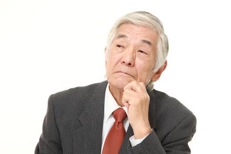 Senior japanischer Geschäftsmann macht sich Sorgen um etwas Standard-Bild