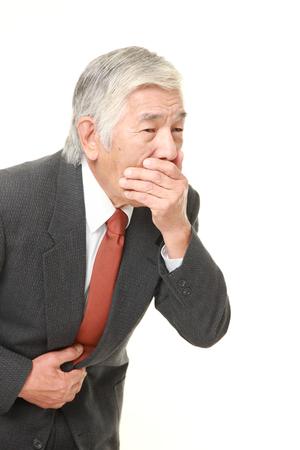 the vomiting: Senior empresario japonés se siente como vómitos Foto de archivo