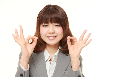 business sign: young Japanese business woman showing perfect sign