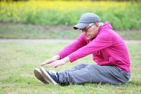 senior Japanese man in a hoodie doing sitting forward bend