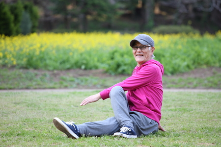 senior Japanese man in a hoodie doing seated torso twist stretch on a lawn
