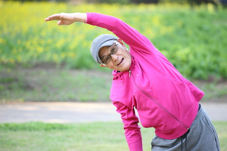 senior Japanese man in a hoodie doing standing side bend exercise