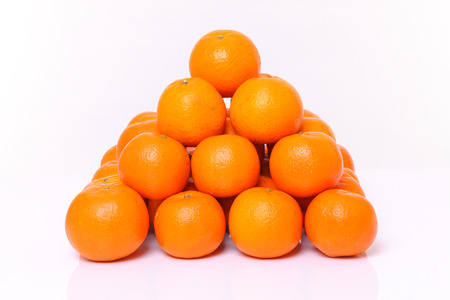 stack of orange fruit citrus tankan against white background