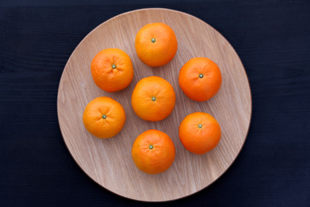 top seven: top view of 7 orange fruit citrus tankan on wooden dish against black background