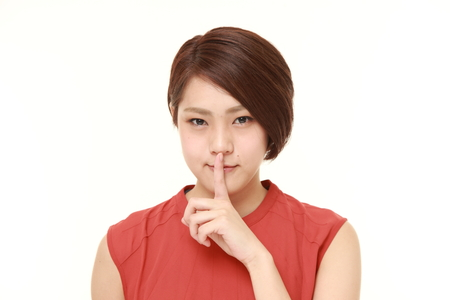 young Japanese woman in a red sleeveless with silence gestures
