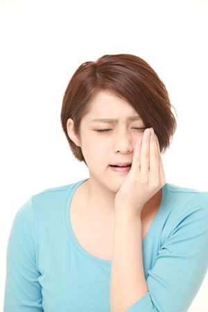 young Japanese woman wearing blue shirt suffers from toothache