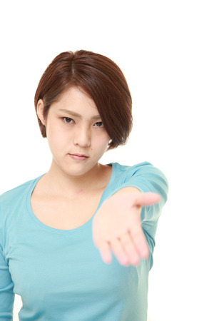 angry young Japanese woman wearing blue shirt demanding something