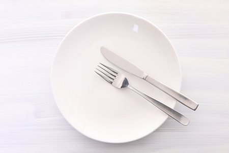 white dish on the white wooden table with cutlery meaning FINISHED