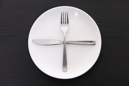 white dish on the black table with cutlery meaning READY FOR NEXT PLATE