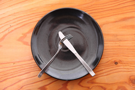 black dish on the wooden table with cutlery meaning DO NOT LIKE Foto de archivo - 114668750
