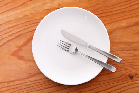 white dish on the wooden table with cutlery meaning FINISHED