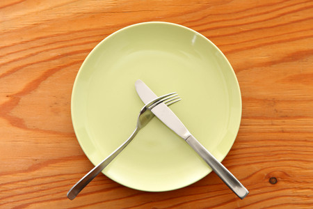 green dish on the wooden table with cutlery meaning DO NOT LIKE Foto de archivo - 114669160