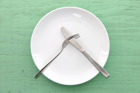 white dish on the green table with cutlery meaning DO NOT LIKE Foto de archivo - 114669358