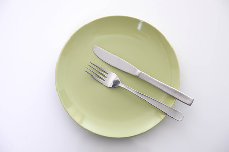 green dish on the white table with cutlery meaning FINISHED Stock Photo