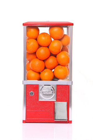 orange fruits in capsule toy vending machine against white background
