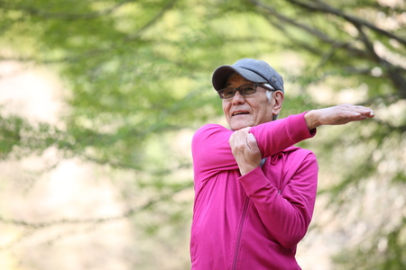senior Japanese man wearing pink parka doing arm stretch outdoor