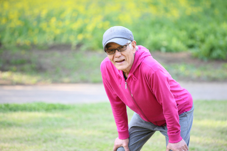 tired senior Japanese man in pink wear resting after workout outdoors Stock fotó