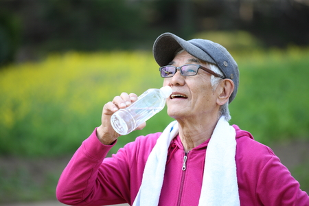 senior Japanese man in pink wear sweaty and thirsty after exercise drinks water outside Stockfoto