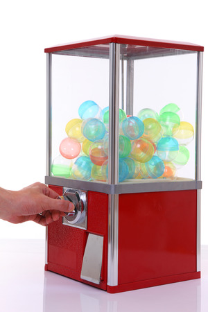 capsule toy vending machine with hand turn a lever isolated on white Banco de Imagens