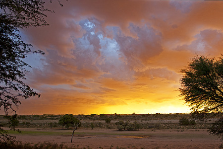 kgalagadi: Sunset over waterhole at Urikaruus desert camp in Kgalagadi Transfrontier park.