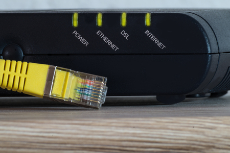 luminous leds of a dsl modem with a yellow network cable 写真素材