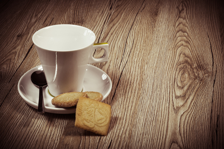 a empty coffee cup on a wooden table. With some cookies. Stock Photo