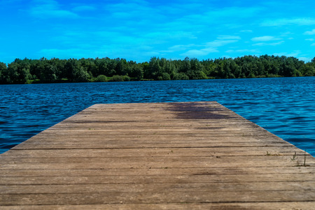 A wooden pier leads into a lake. A sunny day at a german lake. Forest background and cloudy sky. Banco de Imagens