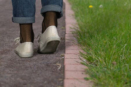 Womens legs in blue jeans and fashionable white sneakers. Young woman walks down a way in park. Close-up. Фото со стока