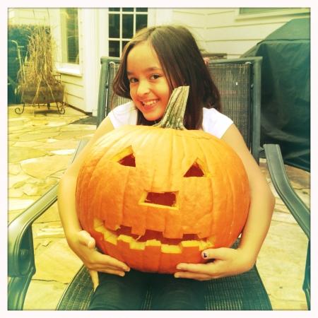 Little girl holding carved pumpkin Stock fotó