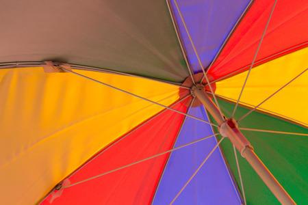 rainbow umbrella: a colorful rainbow colored beach umbrella seen from below