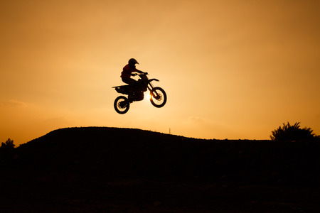motor race: motorcycle silhouette are jumping