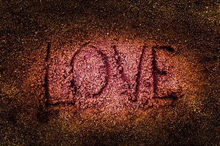 sand drawing: drawing love on sand background