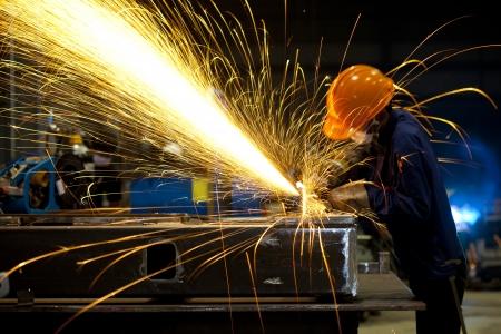 dělník: Tovární dělník pomocí elektrické brusky - série Metal průmysl obrázků