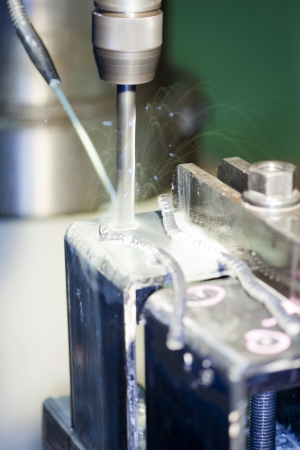 Drilling into a block of metal with a lot of cuttings Stock Photo