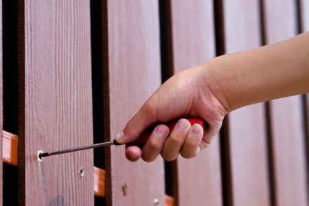 A hand screw in the screw with red screw driver isolated with on walls