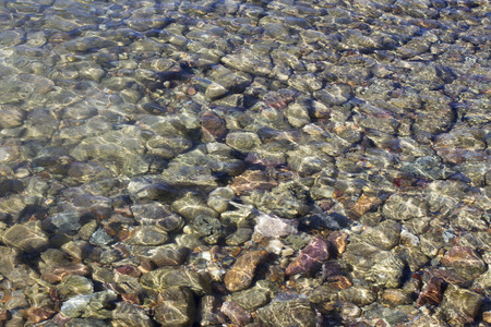 pebbles under water with the sun reflected in water photo