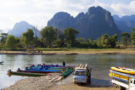 lao: VANG VIENG, LAO P D R Unidentified men are preparing completion for tourists to take long-tailed boat tour in Song River in Vang Vieng, Lao P D R Editorial